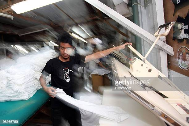 Worker presses a garment after the silkscreening process at the PT Caladi Lima Sembilan garment factory in Bandung, West Java, Indonesia, on...