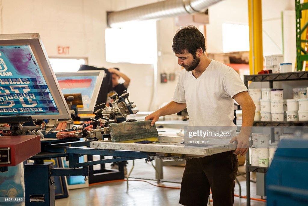 Worker pressing ink on frame in screen printing workshop : Stock Photo