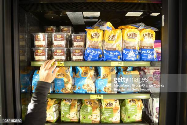 A worker prices items in a refrigerated case at the new Grocery Outlet in Costa Mesa on Monday Beckham said she is helping to get this store open but...