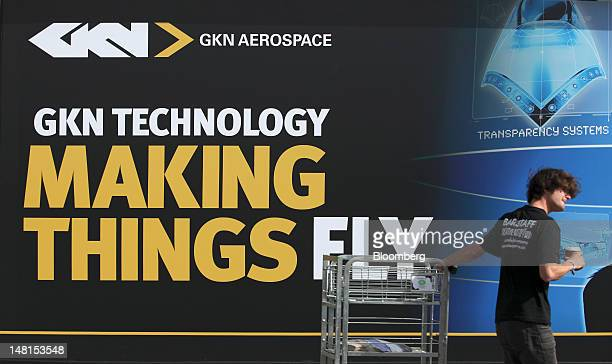 A worker pulls a cage past an advertising poster for GKN Plc on the third day of the Farnborough International Air Show in Farnborough UK on...