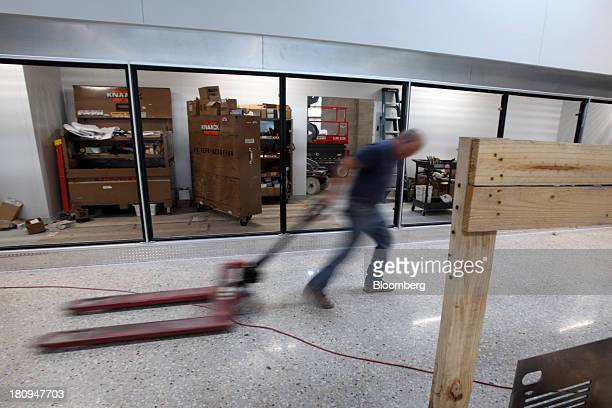 Worker pulls a hand fork lift inside a new Whole Foods Market Inc. Store under construction in Park Ridge, Illinois, U.S., on Tuesday, Sept. 17,...