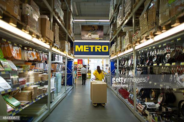 A worker pulls a pallet truck loaded with product boxes along an aisle of homewares inside a Metro Cash Carry store the Russia unit of Metro AG in...