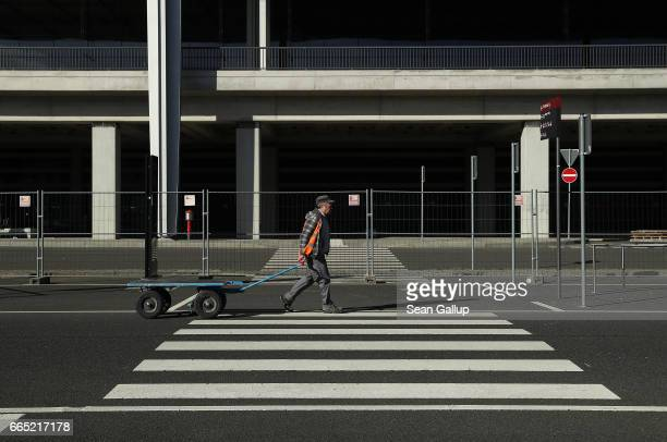 A worker pulls a trolley in front of the main terminal at the stillnotfinished BER Willy Brandt Berlin Brandenburg International Airport on April 6...
