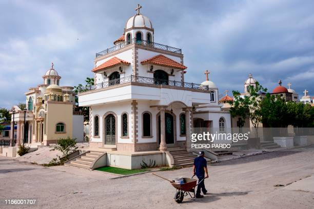 A worker pulls a wheelbarrow at the Jardines del Humaya cemetery known due to its mausoleums where drug traffickers are buried that count with...