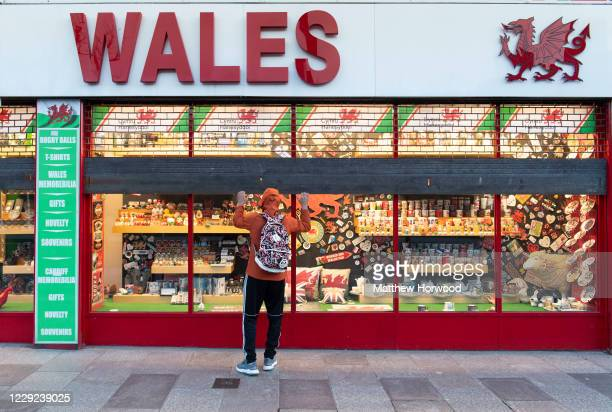 Worker pulls down shutters on a Wales souvenir store in the city centre on October 23, 2020 in Cardiff, Wales. Wales will go into a national lockdown...