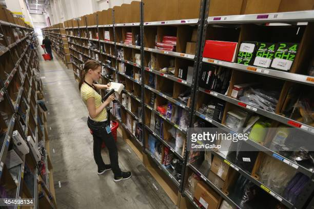A worker pulls items for an order among shelves lined with goods at an Amazon warehouse on September 4 2014 in Brieselang Germany Germany is online...