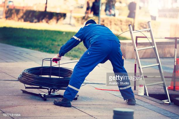 worker pulls the fiber optic cable - fibre optic stock pictures, royalty-free photos & images