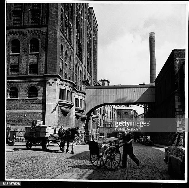 A worker pushes a barrow containing malt samples with part of the vast Guinness complex in the background at St James' Gate brewery Dublin | Location...