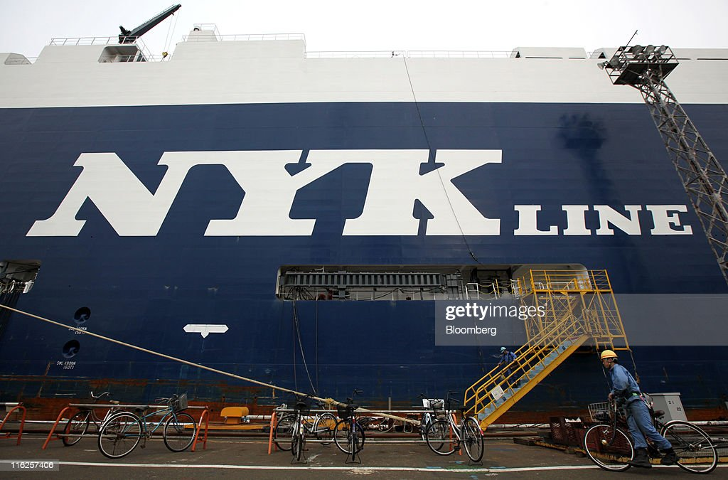 A worker pushes a bicycle past the Nippon Yusen K.K.'s car transporter ship, Auriga Leader, at the Honmoku plant in Yokohama city, Kanagawa prefecture, Japan, on Wednesday, June 15, 2011. Nippon Yusen K.K. is Japan's largest shipping line. Photographer: Tomohiro Ohsumi/Bloomberg via Getty Images