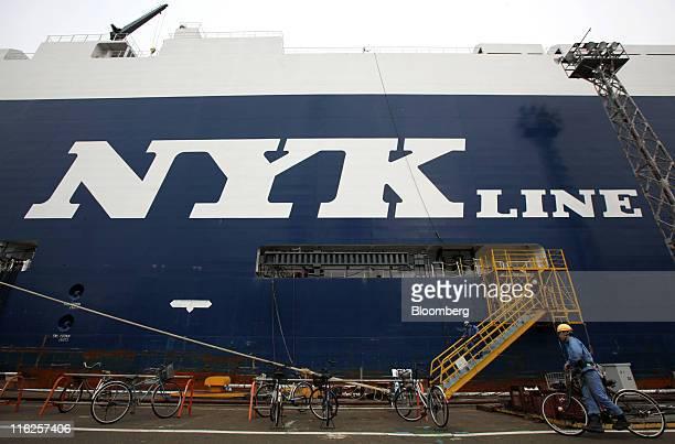 A worker pushes a bicycle past the Nippon Yusen KK's car transporter ship Auriga Leader at the Honmoku plant in Yokohama city Kanagawa prefecture...