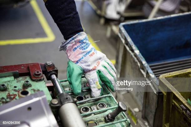 A worker pushes a button to operate machinery at the Mitsubishi Motors Corp manufacturing plant in Santa Rosa Laguna the Philippines on Monday Feb 6...