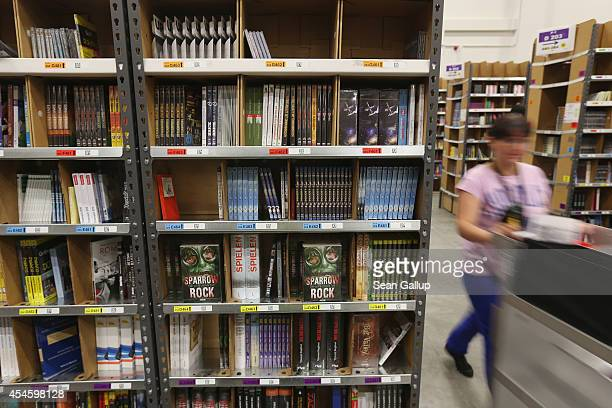 A worker pushes a cart among shelves lined with books and DVDs at an Amazon warehouse on September 4 2014 in Brieselang Germany Germany is online...