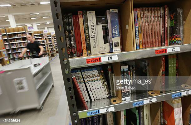 A worker pushes a cart among shelves lined with books at an Amazon warehouse on September 4 2014 in Brieselang Germany Germany is online retailer...