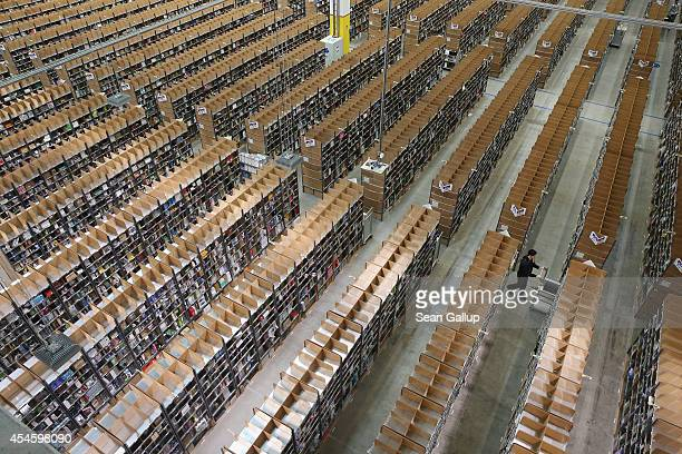 A worker pushes a cart among shelves lined with goods at an Amazon warehouse on September 4 2014 in Brieselang Germany Germany is online retailer...