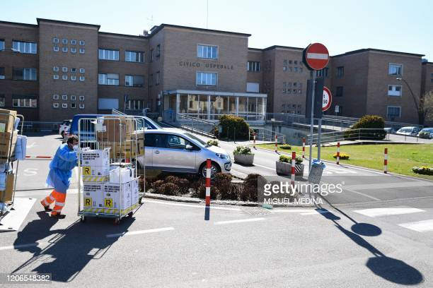 A worker pushes a cart at the hospital in Codogno southeast of Milan on March 11 2020 a day after Italy imposed unprecedented national restrictions...