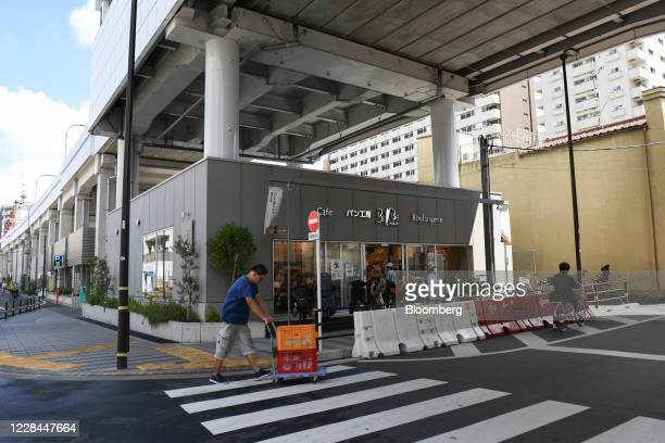 Worker pushes a cart in front of a cafe built under railway tracks in Tokyo, Japan, on Thursday, Sept. 3, 2020. In Tokyo, the spaces beneath elevated...