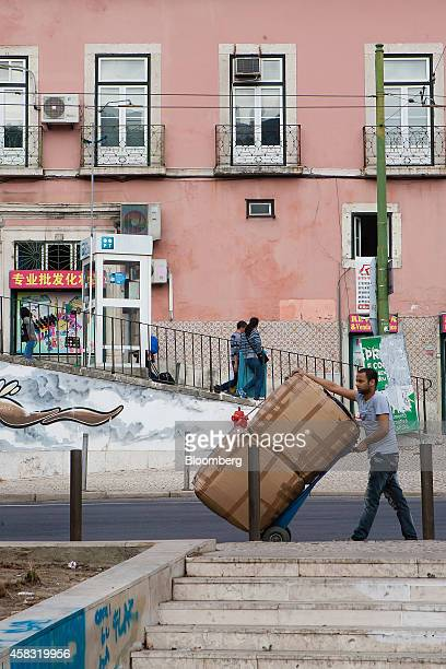 A worker pushes a cart loaded with large boxes of imported goods outside a Chinese supermarket left near Martim Moniz square where Chinese buyers...
