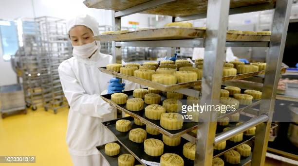 A worker pushes a cart of mooncakes at a mooncake factory on August 21 2018 in Meishan Sichuan Province of China Mooncake is the traditional food for...