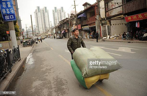 A worker pushes a cart outside a wholesale clothing market in Shanghai on February 25 2013 China's manufacturing growth hit a fourmonth low in...