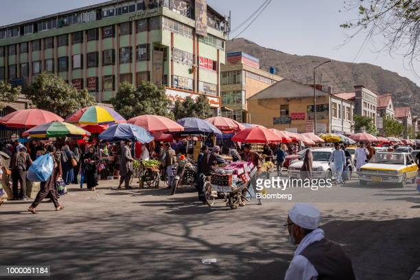 A worker pushes a cart past shoppers and stalls in a street market in Kabul Afghanistan on Thursday July 12 2018 US President Donald last year said...