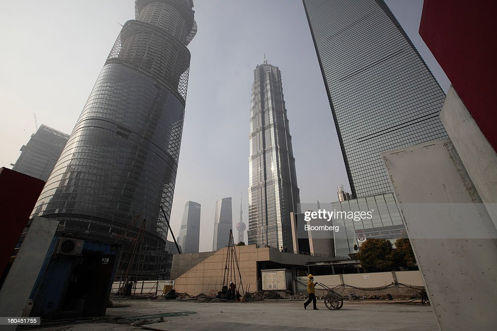 A worker pushes a cart through a construction site for a commercial building in the Pudong area of Shanghai, China, on Wednesday, Jan. 30, 2013. China's economic growth accelerated for the first time in two years as government efforts to revive demand drove a rebound in industrial output, retail sales and the housing market. Photographer: Tomohiro Ohsumi/Bloomberg via Getty Images