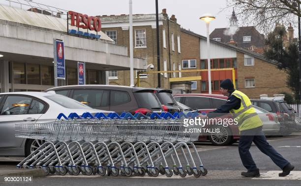 A worker pushes a line of trolleys in the car park at a branch of Tesco in south London on January 9 2018 / AFP PHOTO / Justin TALLIS