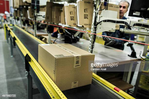 A worker pushes a packed order at an Amazon warehouse on November 17 2015 in Brieselang Germany Germany is online retailer Amazon's second largest...