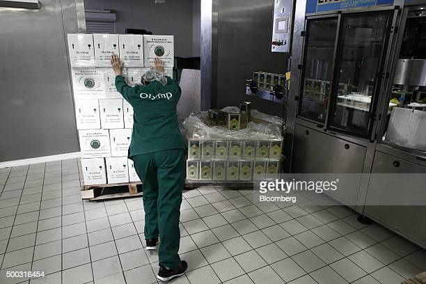 Worker pushes a palette of olive oil cans in the bottling and processing plant operated by the Messina Union in Kalamata, Greece, on Friday, Dec. 4,...