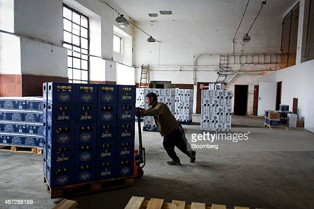 A worker pushes a pallet truck loaded with crates of Zatec beer in a distribution room at the Zatecky Pivovar brewery in Zatec Czech Republic on...