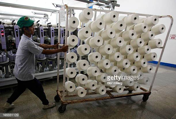 A worker pushes a rack holding spools of yarn in the spinning area at a PT Sri Rejeki Isman factory in Sukoharjo Java Indonesia on Wednesday March 27...