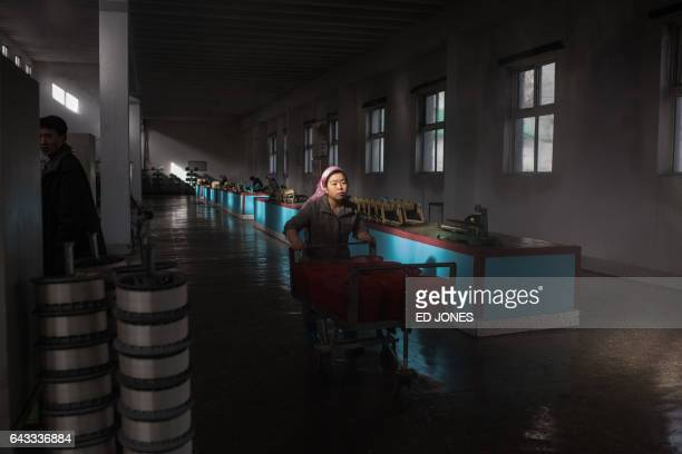 TOPSHOT A worker pushes a trolley carrying buckets of silkworm larvae at the Kim Jong Suk Silk Mill in Pyongyang on February 21 2017 The Kim Jong Suk...