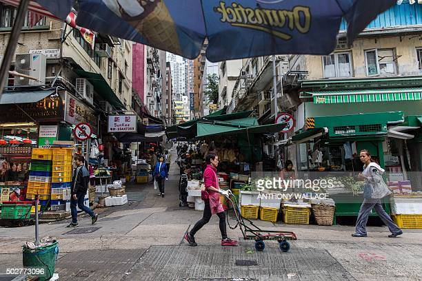 A worker pushes a trolley past stalls on Gage Street the site of one of the oldest wet markets in Hong Kong on December 29 2015 Vendors have been...