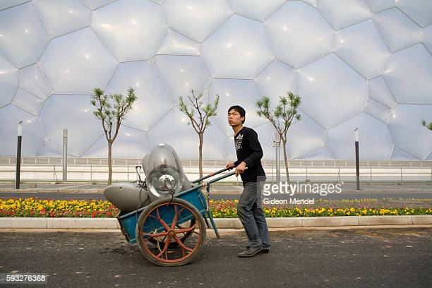 Worker pushes a trolley past the newly constructed National Aquatics Center, known as the Water Cube, in the new Olympic Green in Beijing. The...