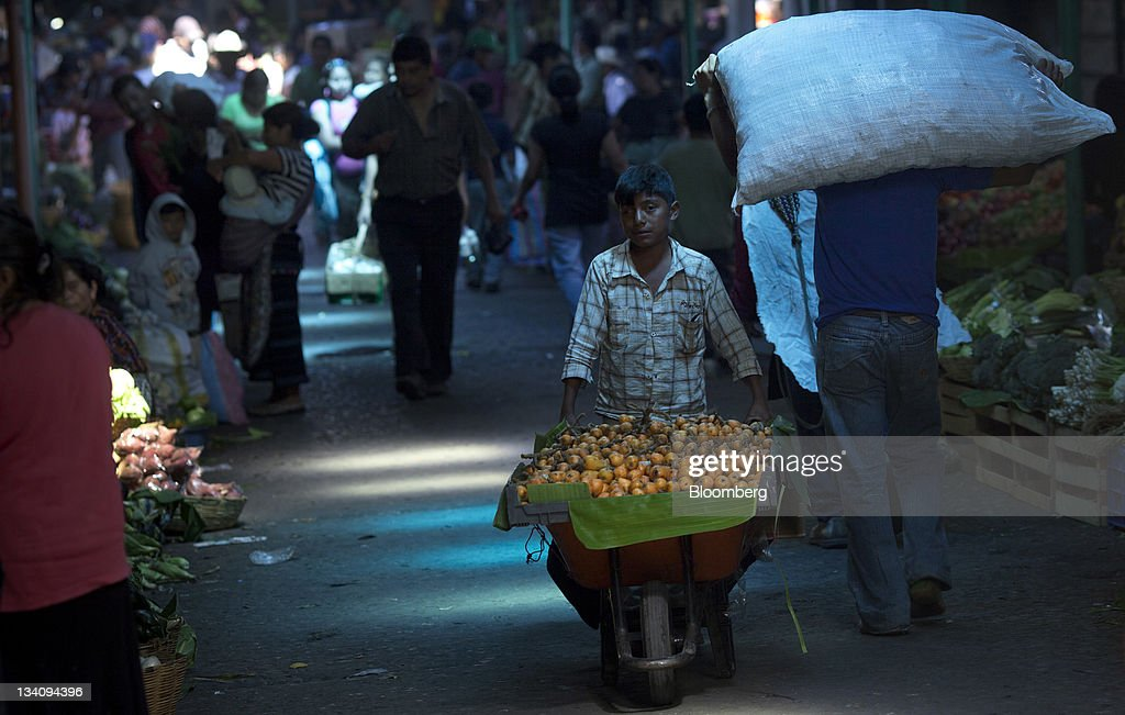 A worker pushes a wheelbarrow carrying produce at the Terminal Market in Guatemala City, Guatemala, on Wednesday, Nov. 23, 2011. Foreign direct investment in Guatemala will stagnate this year at about $668 million, after rising 22 percent in 2010, according to the International Monetary Fund (IMF). Photographer: Victor J. Blue/Bloomberg via Getty Images