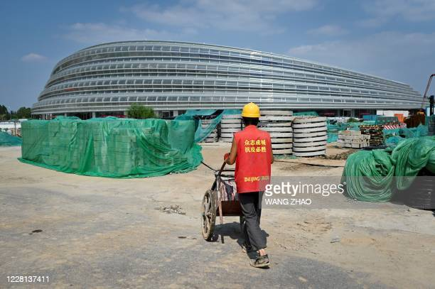 A worker pushes a wheelbarrow towards the underconstruction National Speed Skating Oval the venue for speed skating events at the Beijing 2022 Winter...