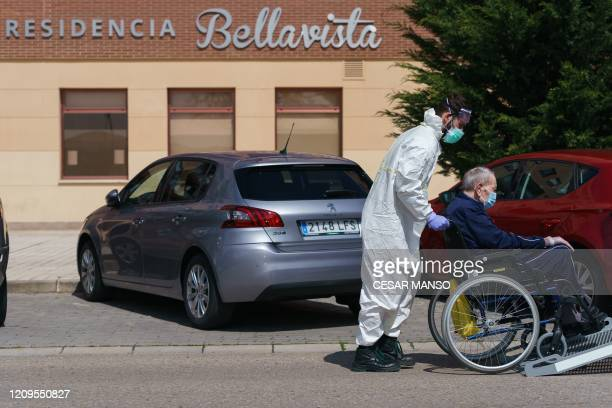 A worker pushes an elder man on a wheelchair outside an elderly people nursing home in Burgos in northern Spain on April 9 2020 Spain's daily death...