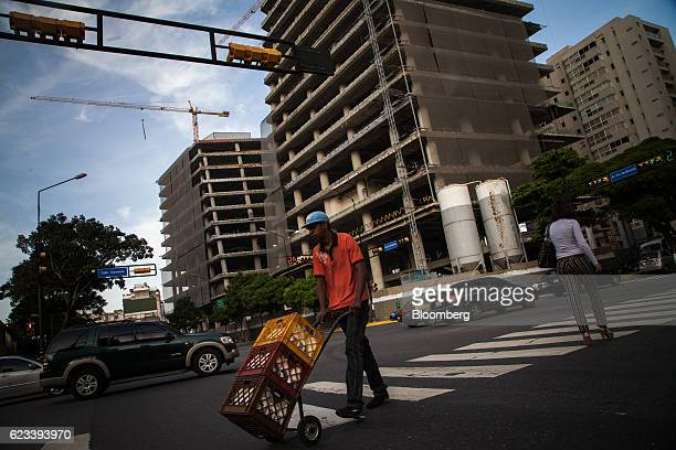 A worker pushes crates of milk while passing in front of a commercial building under construction in the La Castellana neighborhood of Caracas...