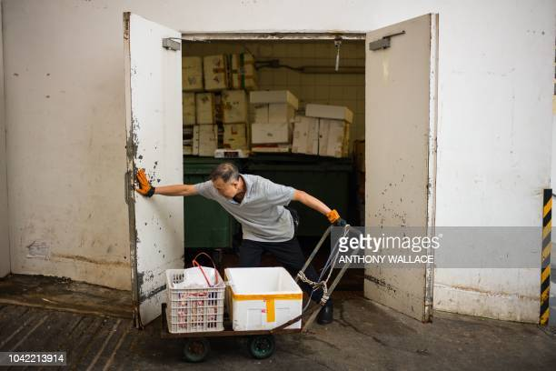 A worker pushes open the doors of a refuse room at the Choi Wan public housing estate in Hong Kong on September 28 where there were signs of rat...