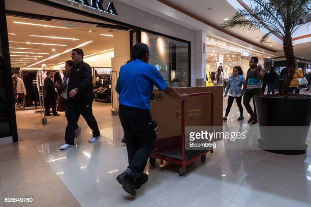 A worker pushes trolley carrying an LG Electronics Inc high definition television at the Forum Buenavista mall in Mexico City Mexico on Monday Nov 20...
