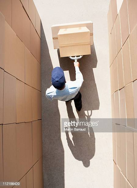 Worker pushing boxes on hand truck