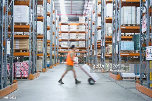 worker pushing hand truck in warehouse - 倉庫 ストックフォトと画像