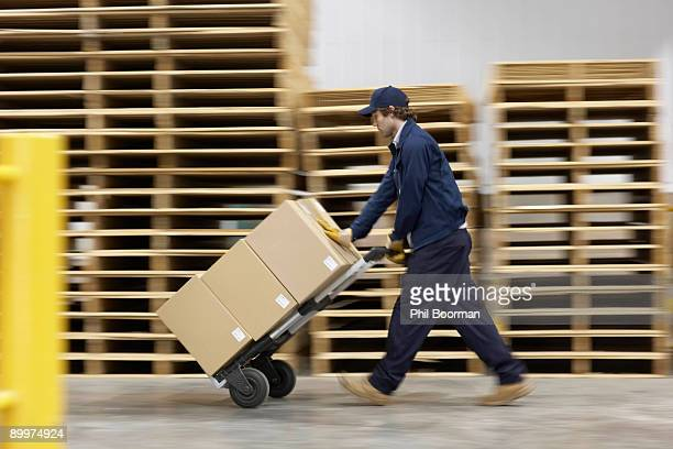 worker pushing trolley in warehouse - sack barrow stock pictures, royalty-free photos & images