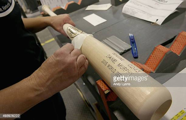 A worker puts a decal on a 2015 World Series bat of Daniel Murphy of the New York Mets at the Louisville Slugger Museum and Factory on October 23...