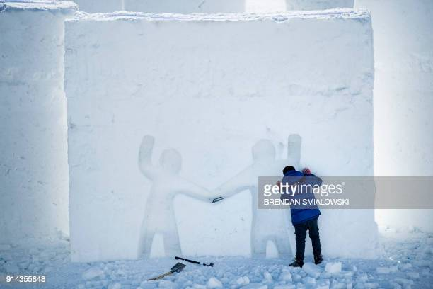 A worker puts final touches on Snow Land before the PyeongChang 2018 Winter Olympic Games in PyeongChang on February 5 2018 / AFP PHOTO / Brendan...