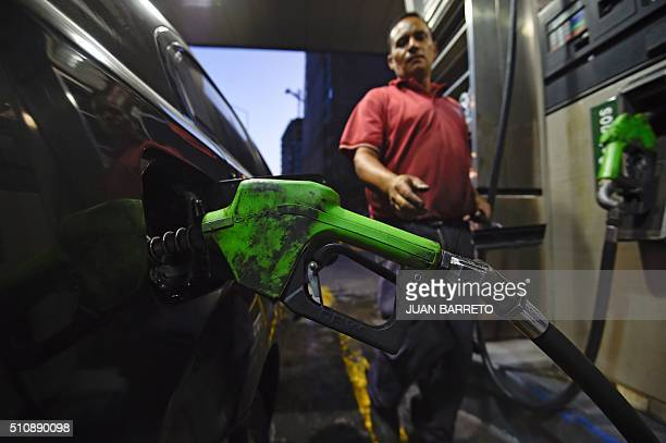 A worker puts gas to a vehicle in Caracas on February 17 2016 Venezuela's President Nicolas Maduro said Wednesday he would raise the price of...