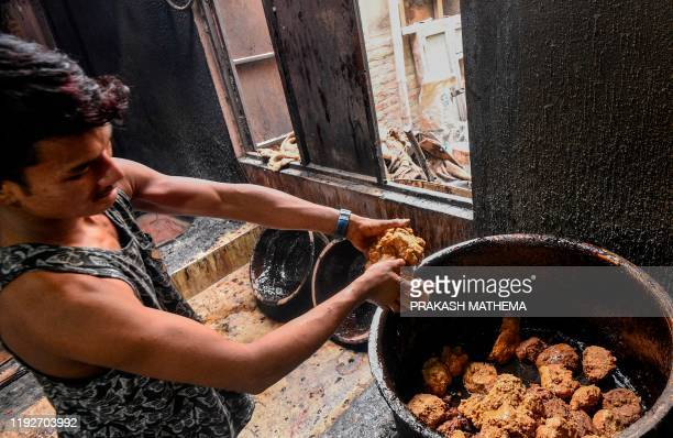 A worker puts jaggery to be boiled in a pot to make molasses locally know as Chaku for the upcoming Maghe Sankranti festival in Tokha on the...