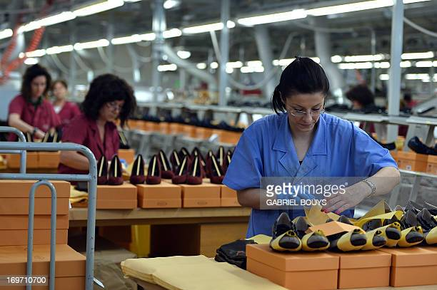 Worker puts pairs of shoes in boxes in the factory of the Italian shoes and luxury leather goods Tod's on May 28, 2013 at the headquarters of the...