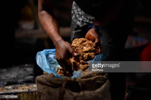 A Worker puts Raw Hard molasses boiling to prepare molasses Chaku at Tokha Kathmandu Nepal on January 10 2020 Molasses Chaku is usually prepared and...