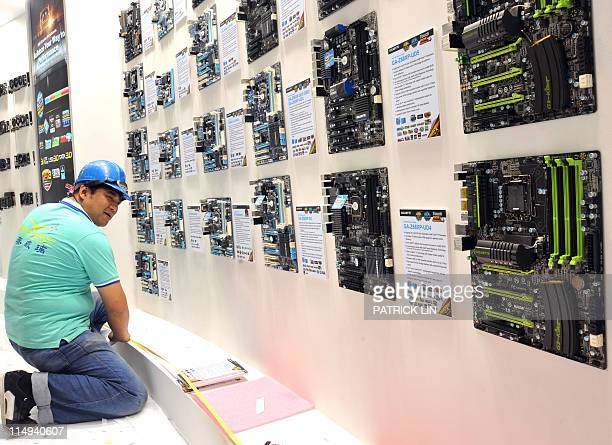 A worker puts the final touch to a booth of Gigabyte a leading Taiwan IT product maker on the eve of Asia's biggest IT trade fair on May 30 2011 The...