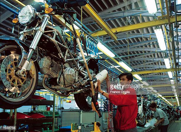 A worker puts the final touches on a fully produced Ducati Monster at the Ducati factory September 12 2002 in Borgo Panigale Bologna Italy Ducati...